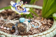 Jewelery made of natural stones against the backdrop of blossoming pasiflora. Bracelets, rings, necklaces, handmade earrings close. Up. The texture of natural stock photo