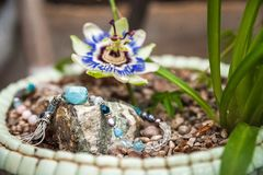 Jewelery made of natural stones against the backdrop of blossoming pasiflora. Bracelets, rings, necklaces, handmade earrings close. Up. The texture of natural royalty free stock photography