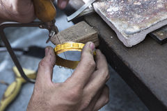 Jewelery making. Close up of Jeweler crafting golden bangle with flame torch Royalty Free Stock Image