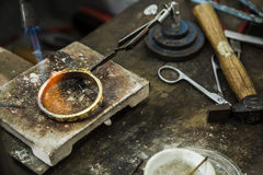 Jewelery making. Close up of Jeweler crafting golden rings with flame torch Royalty Free Stock Photos