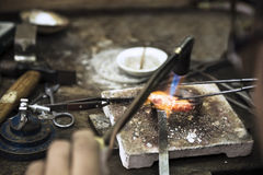 Jewelery making. Close up of Jeweler crafting golden rings with flame torch Stock Image