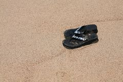 Jewelled dirty sandals in the sand Royalty Free Stock Image