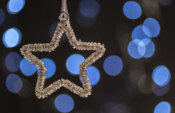 Jewelled star Christmas ornament. With blurred blue lights in the background stock photos