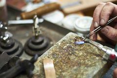 Jeweller. Uses blow torch to manufacter a gold ring Stock Images