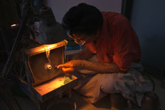 Jeweller at work on ruby stone in jaipur. Indian craftsman with nose to the grinding wheel works on a ruby attached to a stick. fairtrade,working conditions royalty free stock image