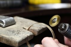 Jeweller working with bracelet by polishing motors tool. Jewelry workplace. Stock Image