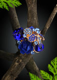 Jewellery blue ring as flower on twig, dark background Stock Images