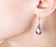 Jewellery ear-ring in an ear. Beautiful jewellery ear-ring in an ear of young woman Royalty Free Stock Image