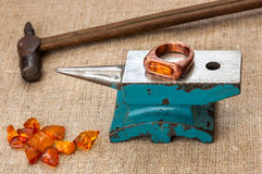 Jewellery forging. On an anvil the ring with an amber insert lies. nearby there is hammer and small group of amber Stock Photo