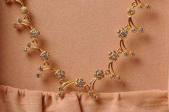 Jewellery. Gold necklace jewellery on textured fabric background Stock Image