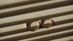 Gold wedding rings on a on wooden window blinds in backlight macro closeup lens flare shoot diamon jewellery. Jewellery macro highlight wedding rings couple stock footage
