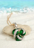 Jewellery pendant on sand beach with sea background, soft focus. Jewellery pendant with emeralds on sand beach, soft focus Royalty Free Stock Photo