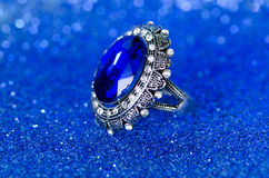 The jewellery ring against blue background Royalty Free Stock Photos