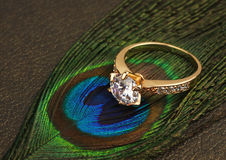 Jewellery ring with big diamond on dark feathers background Stock Images