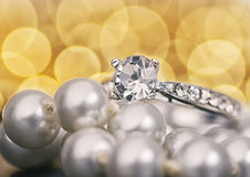 Jewellery. Silver ring with diamonds and pearls on a background of yellow light Stock Image