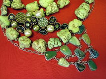 Jewelry. Various green natural stone jewelry on red background Royalty Free Stock Images