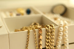 Jewelry. Gold and pearl jewelry in a jewelry box. Focus on the jewelry in front, oof area for your text Royalty Free Stock Image