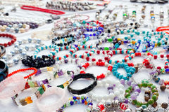 Jewelry in a bargain market spread. Jewelry mixed in a bargain market spread on white fabric Stock Images