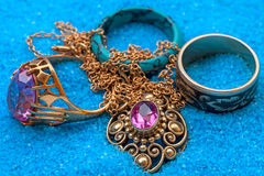 Jewelry in blue sand Stock Photography