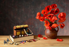 Jewelry, books and poppies in a vase Stock Photography