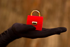 Jewelry box. Hand in glove holding red jewelry box Royalty Free Stock Images