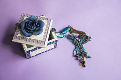 Jewelry box with blue turquoise glass beads necklace. Jewelry box with blue turquoise glass beads necklace on violet background. Modern fashion art. Artistic Stock Photography