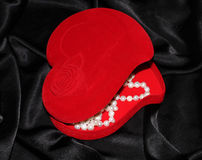 Jewelry box in the form of heart. Red heart-shaped jewelry box with pearl on a black silk Royalty Free Stock Photography