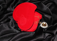 Jewelry box in the form of heart. Red heart-shaped jewelry box with pendan on a black silk Royalty Free Stock Photos