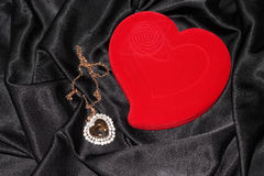 Jewelry box in the form of heart. Red heart-shaped jewelry box with pendan on a black silk Royalty Free Stock Image