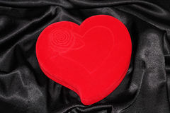 Jewelry box in the form of heart. Red heart-shaped jewelry box with pendan on a black silk Stock Images