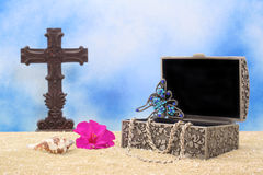 Jewelry Box on Sand. With Cross and Blue Sky Background Royalty Free Stock Photo