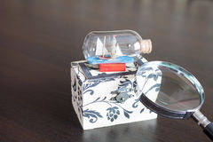 Jewelry box with a ship and a magnifying glass Royalty Free Stock Photos