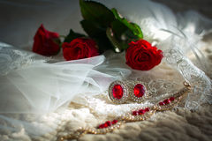 Jewelry for the bride: veil, ear rings, bracelet and red roses Stock Image