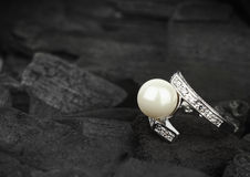 Jewelry with brilliant and pearl on black coal background, soft Royalty Free Stock Photo