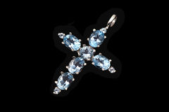 Jewelry cross with blue topaz. Jewelry with blue topaz on black background Royalty Free Stock Photography