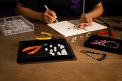 Jewelry designer works on a hand drawing sketch.  royalty free stock image
