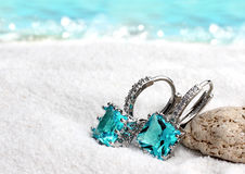 Jewelry earrings with aquamarine on sand beach background, soft. Focus stock image