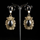 Jewelry earrings with gems. Jewelry filigree earrings with shiny gems on black background Stock Images