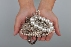 Jewelry in female hands. Pearl and silver Stock Images
