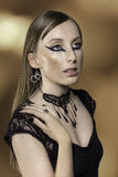 Jewelry. Female model posing with a black necklace and long eyeliner Royalty Free Stock Photos