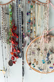 Jewelry and Finery Hanging Against Wall. Jewelry organizer hanging on wall with earrings necklaces pendants and other finery Stock Photos