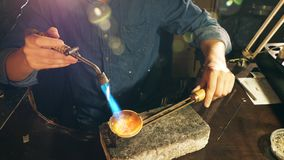 Jewelry is getting heated with the burner in craftsman's hands. 4K stock video footage