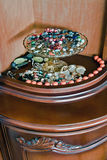 Jewelry on glass tray. Set of varied types of jewelry on and beneath glass tray placed inside showcase Stock Images
