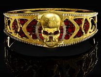 Jewelry gold skull bracelet with diamond and red ruby gems. Royalty Free Stock Image