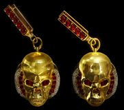 Jewelry gold skull earrings with diamond and red ruby gems. Antiques fingers ring from pirate treasure or hoard may be magic vampire artifact. Luxury Stock Photos