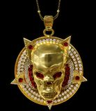 Jewelry gold skull pendant with star pentagram diamond. And red ruby gems. Antiques necklace from pirate treasure or hoard may be magic vampire artifact. Luxury royalty free stock photos