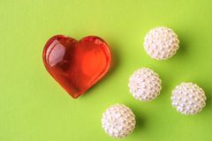 Jewelry heart-shaped and round balls beads lying near the heart. Green background Royalty Free Stock Photos