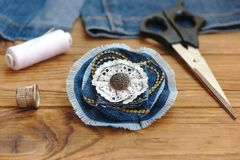 Blue flower brooch or hair accessory. Scissors, thread, thimble, needle, old jeans on a wooden table. Recycle jeans projects Royalty Free Stock Photo