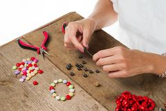 Jewelry making. Making bracelet of colorful beads. Female hands with a tool on a rough wooden table. Selective focus royalty free stock photography