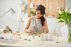 Jewelry making. Concentrated beautiful woman making jewelry pieces at home studio stock photography